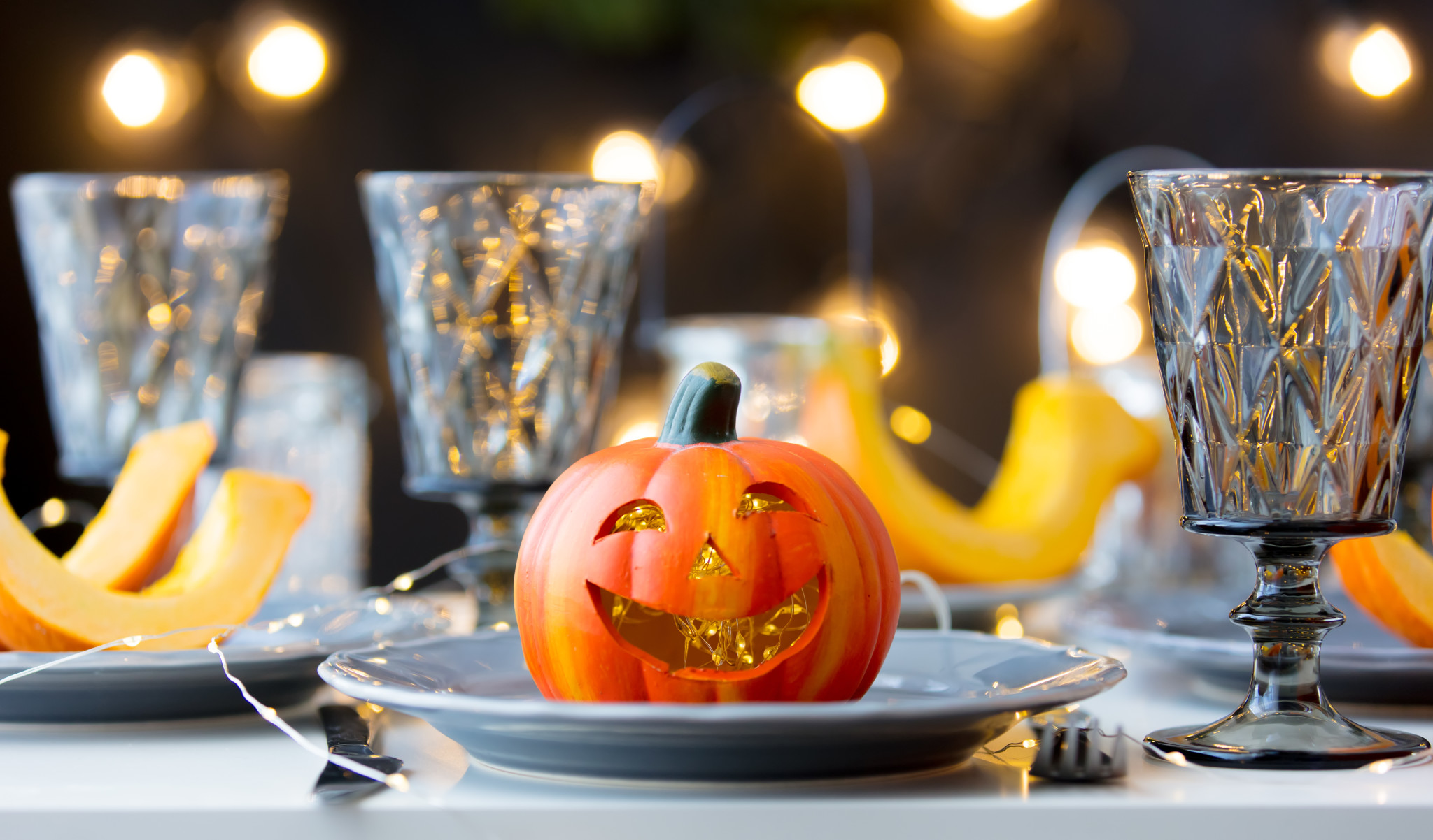 Halloween pumpkin at dishes on dinner with Fairy Ligths on background